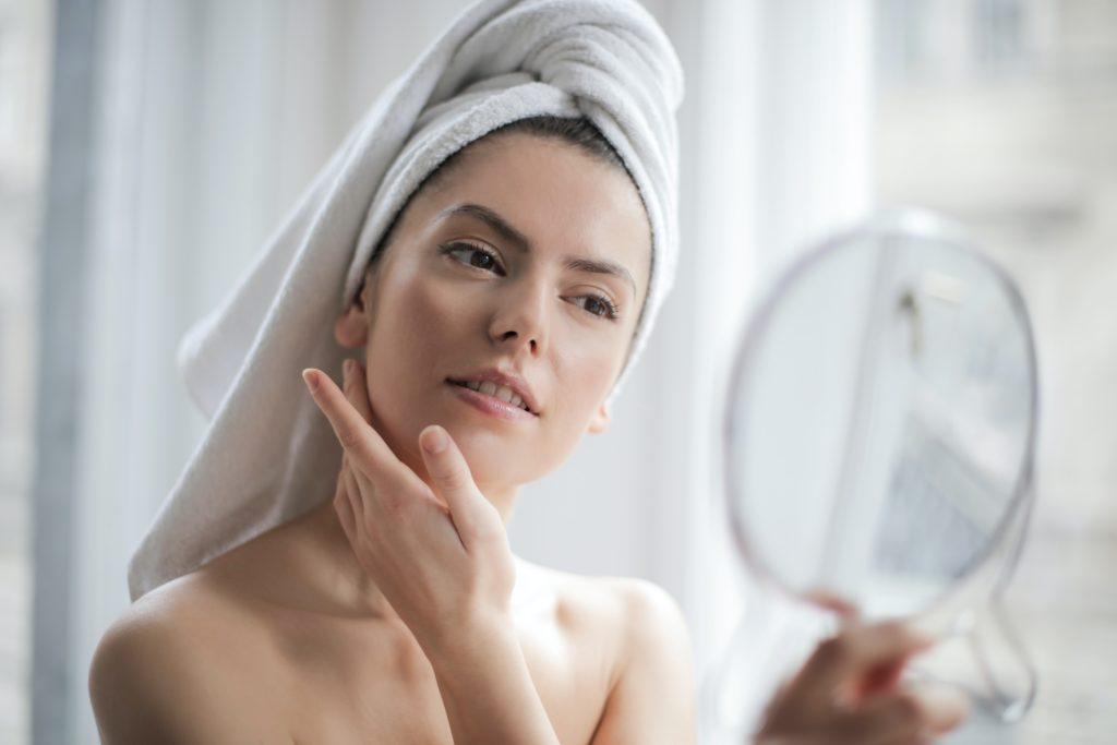 Mulher com toalha no cabelo cuidando da pele e se olhando no espelho