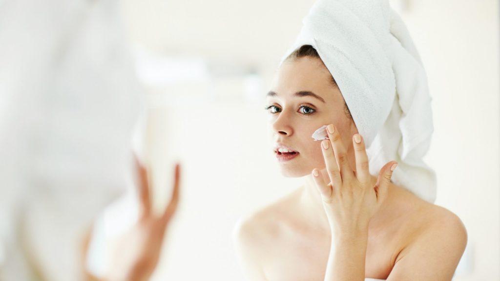 Mulher aplicando creme no rosto, com toalha na cabeça e olhando no espelho