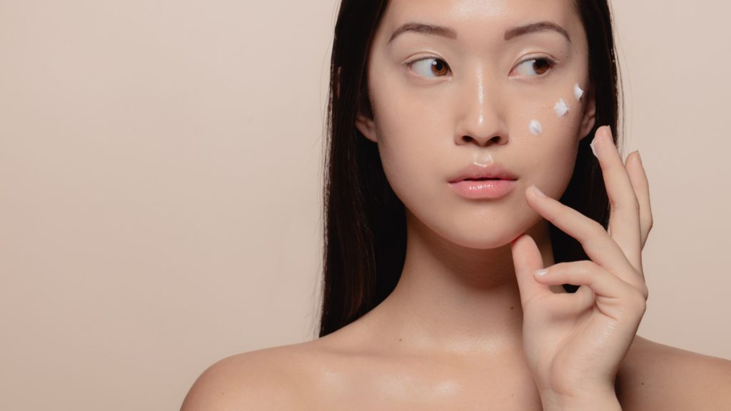 Mulher aplicando creme no rosto com ponta dos dedos