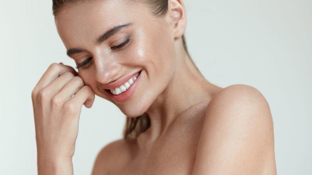 Mulher sorrindo e colocando a mão no rosto